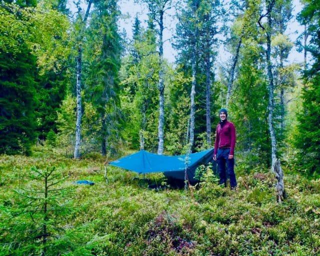Deelnemer Back to the Wild staat bij zijn tarp waar hij onder slaapt tijdens de Wilderness Retreat