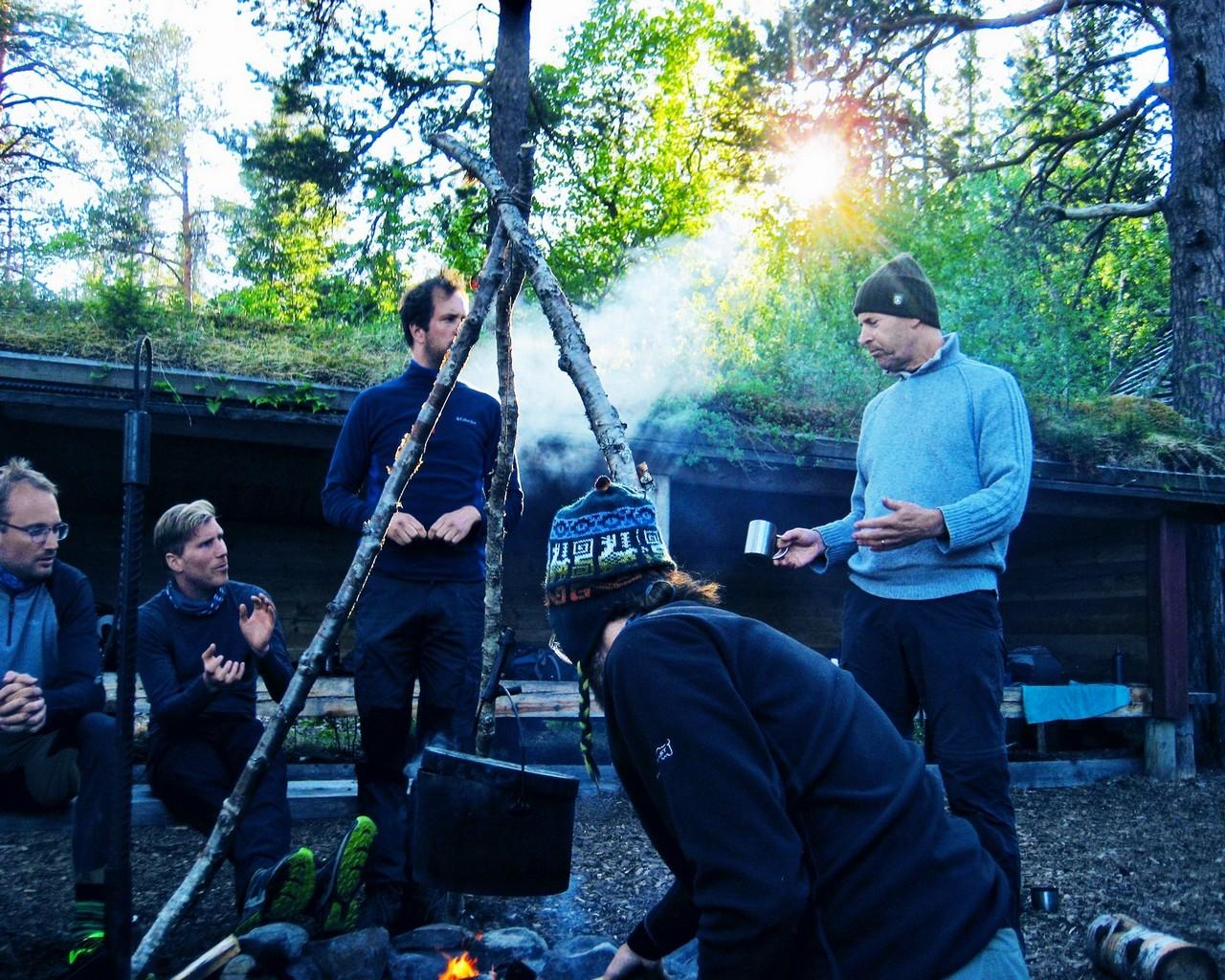 Deelnemers delen verhalen en ervaringen rond het kampvuur